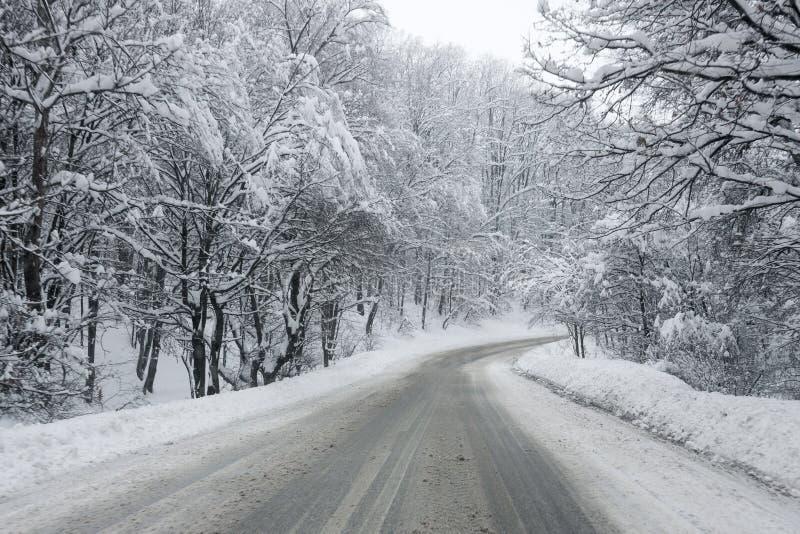 Tung snö på en smutsig hal vinterväg royaltyfri fotografi