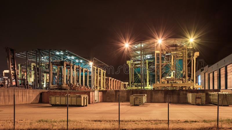 Tung utrustning på den upplysta behållareterminalen på nattetid, port av Antwerp, Belgien arkivbilder