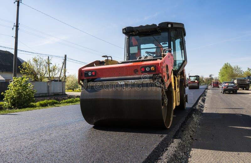 Tung vibrationsrulle på asfalttrottoar som arbetar på den nya vägkonstruktionsplatsen reparera arkivbild
