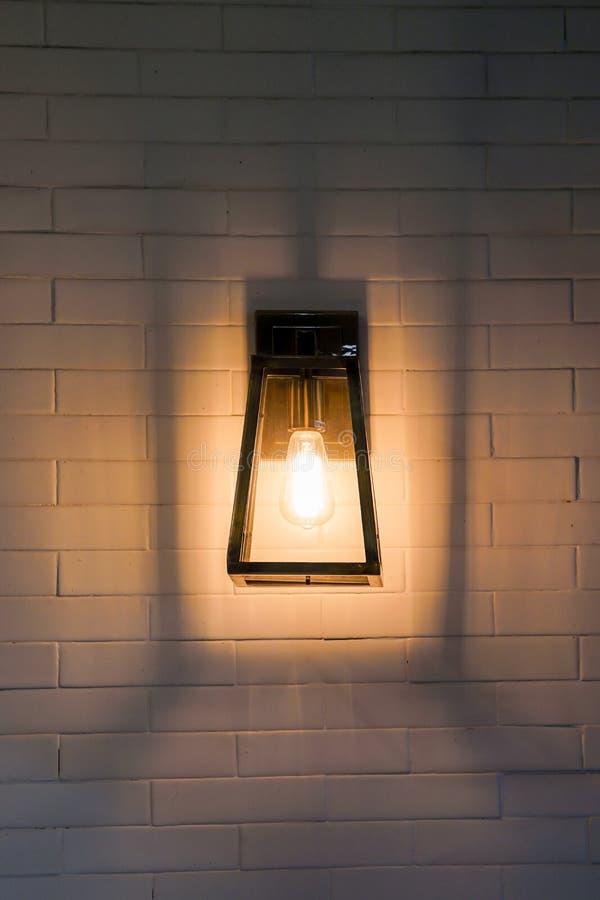 Tungstène en acier de lampe de place/lumière chaude sur le mur de briques blanc photo stock