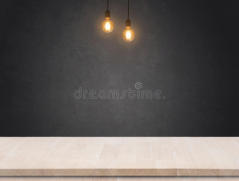 Tungsten light bulb with black cement wall background and wood table. stock photo