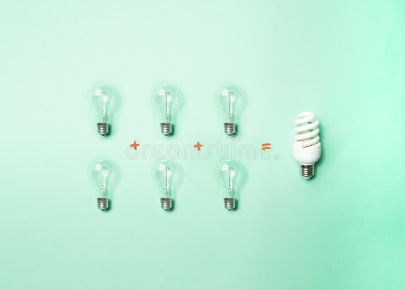 Tungsten light bulbs and energy-saving bulb on green background stock photos