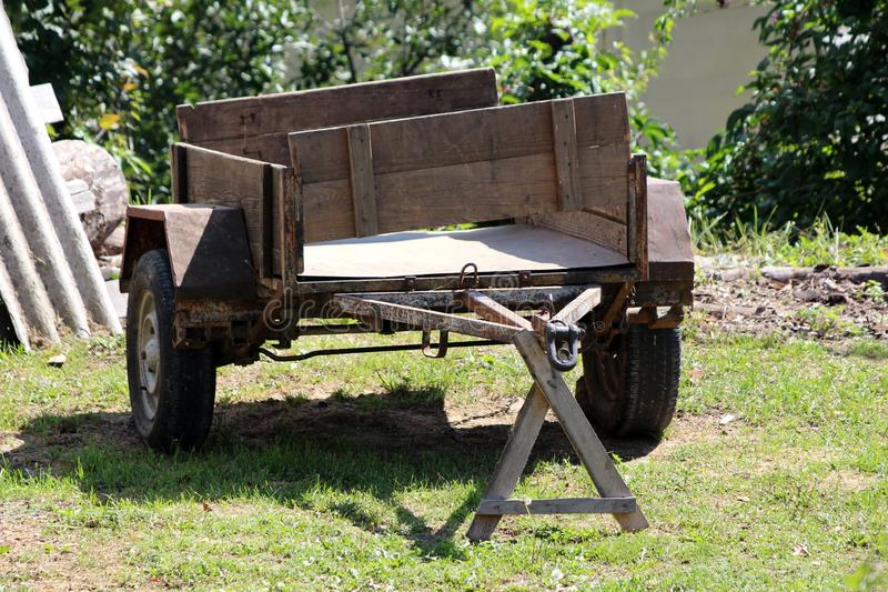 Tungt - använde den gamla bilsläpet med rostad metall, och trädelar lämnade på gräs i trädgården som omgavs med byggnadsmaterial  arkivbild