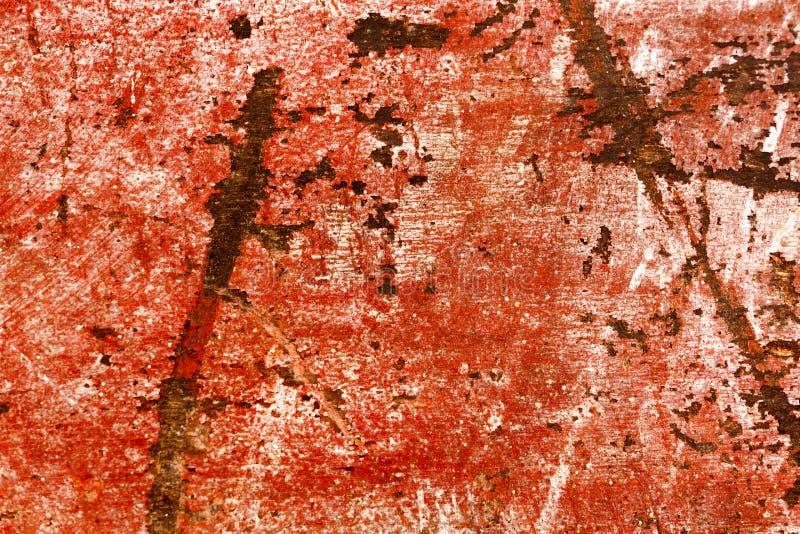 Tungt skadat skrapat stycke av rött målat trä arkivbild
