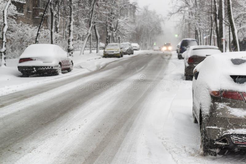 Tungt snöfall och hal väg med parkerade bilar royaltyfri fotografi