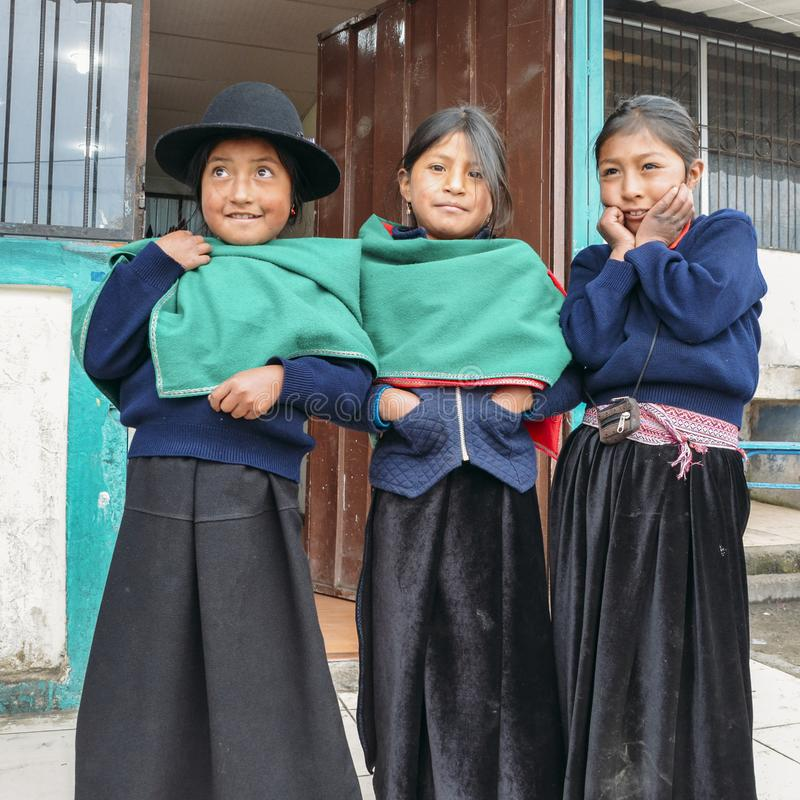 Young Ecuadorian indigenous schoolgirls pose for a picture outside their school royalty free stock photos