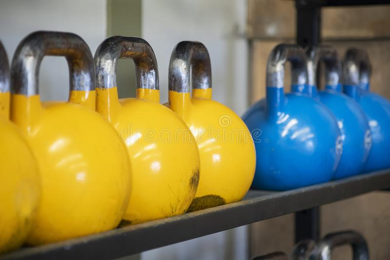 Tungviktuppsättningar av kettlebell på järnkuggar på idrottshallen som används för funktionell kondition, CrossFit för hög styrka arkivbild