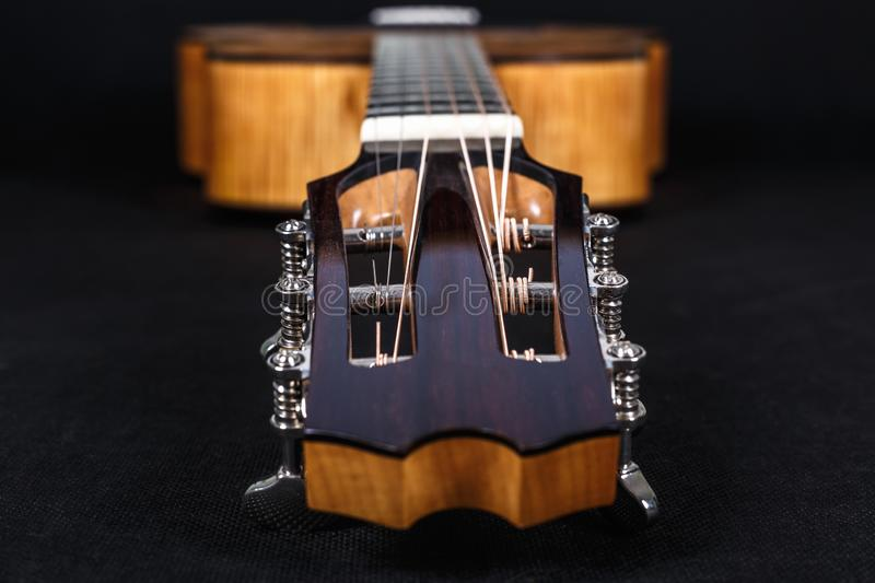 Tuning pegs on wooden machine head of six strings acoustic guitar neck on black background.  stock photography