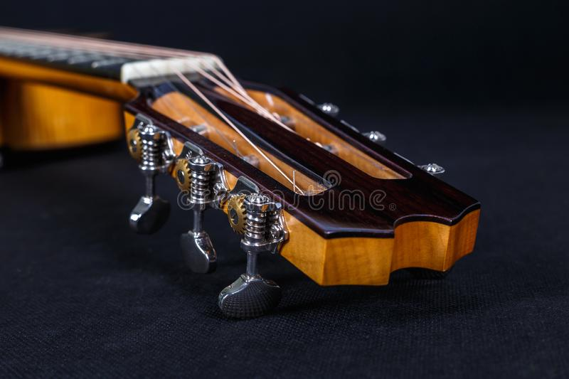 Tuning pegs on wooden machine head of six strings acoustic guitar neck on black background.  stock photos
