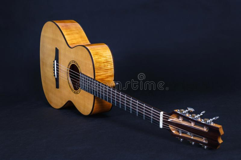 Tuning pegs on wooden machine head of six strings acoustic guitar neck on black background.  stock image