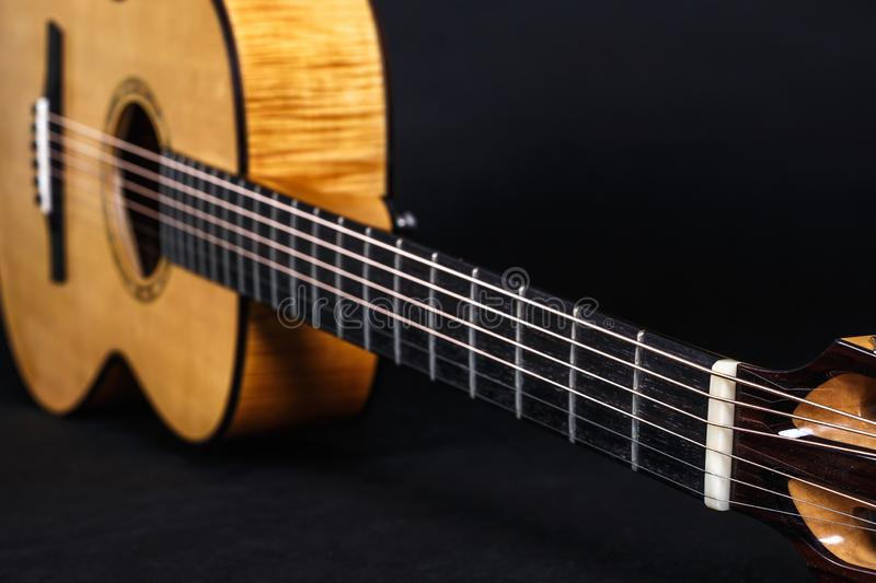 Tuning pegs on wooden machine head of six strings acoustic guitar neck on black background.  royalty free stock image