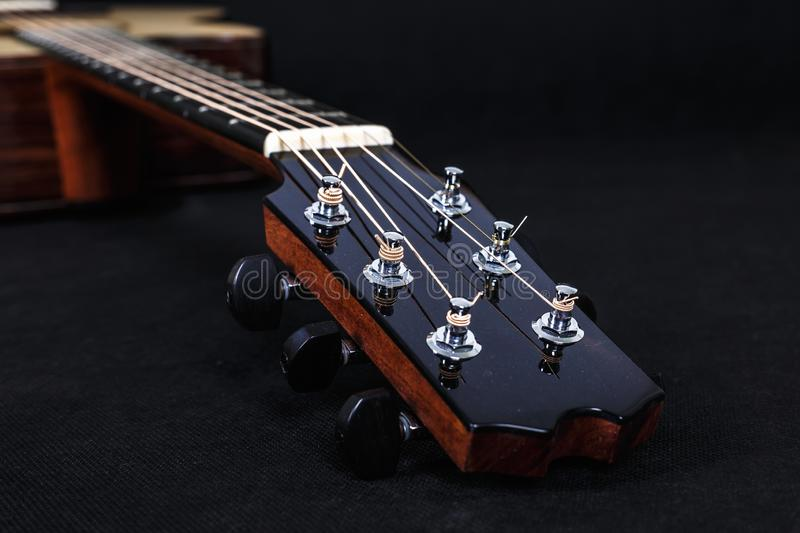 Tuning pegs on wooden machine head of six strings acoustic guitar neck on black background.  royalty free stock photos