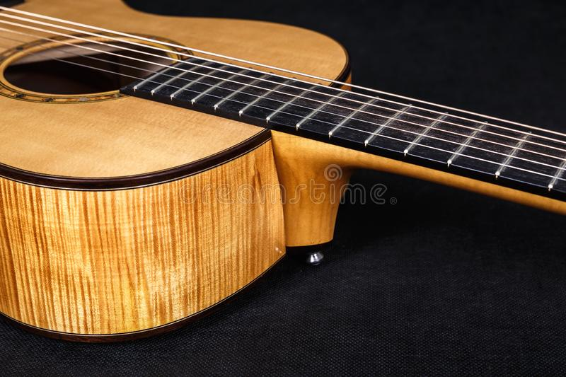 Tuning pegs on wooden machine head of six strings acoustic guitar neck on black background.  royalty free stock photo
