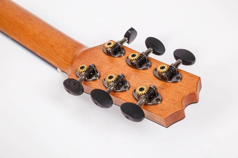 Tuning pegs on wooden machine head of six strings guitar on white background stock photos