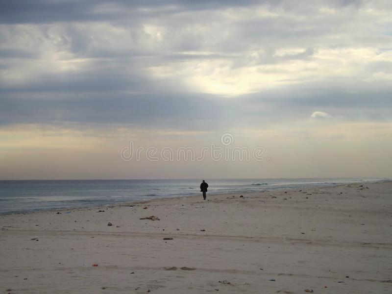 Tunis, North Tunisia, near Hammamet. A lonesome man walking along a sandy beach royalty free stock images