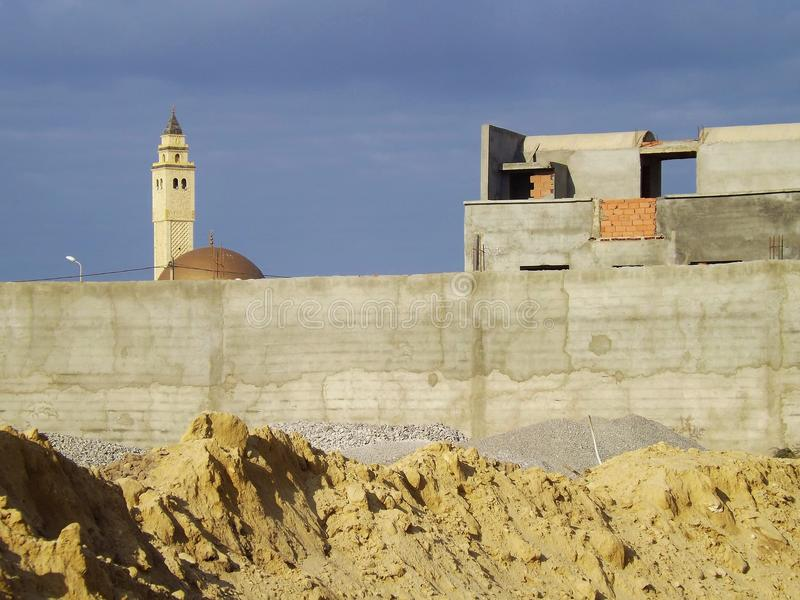 Tunisia, in a village near Hammamet. The minaret of a mosque behind a stone wall stock images
