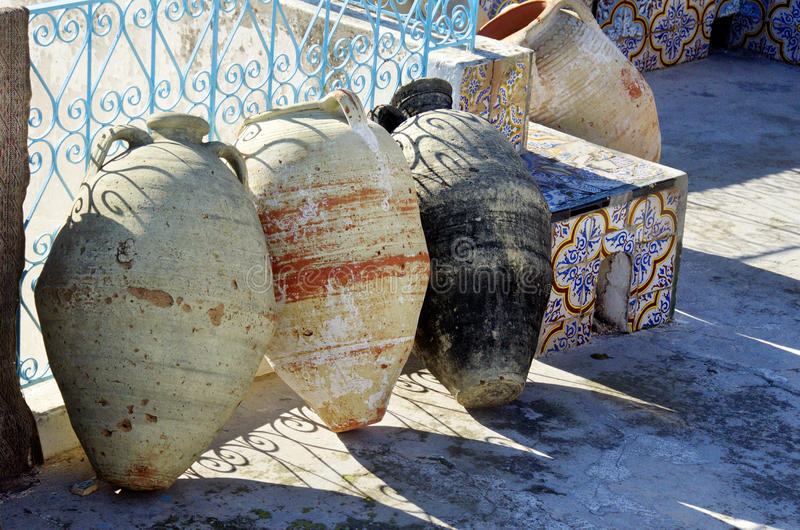 Tunisian amphoras on the floor decorated with ceramic tiles and blue railing in Tunisia royalty free stock photography