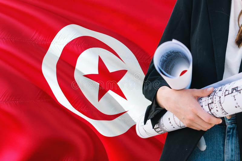 Tunisian Architect woman holding blueprint against Tunisia waving flag background. Construction and architecture concept royalty free stock photography
