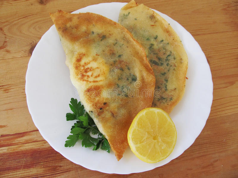Tunisian brik. Traditional Tunisian dish brik on a white plate. Served with lemon stock images