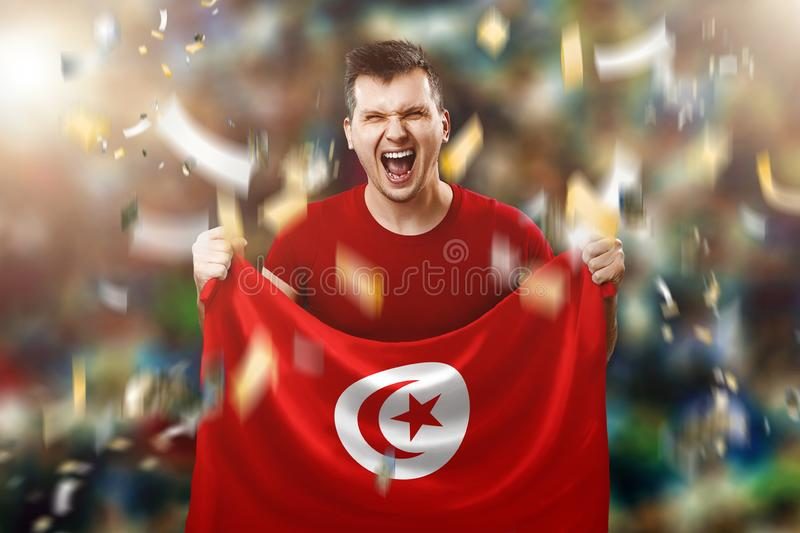 Tunisian fan, fan of a man holding the national flag of Tunisia in his hands. Soccer fan in the stadium. Mixed media stock image