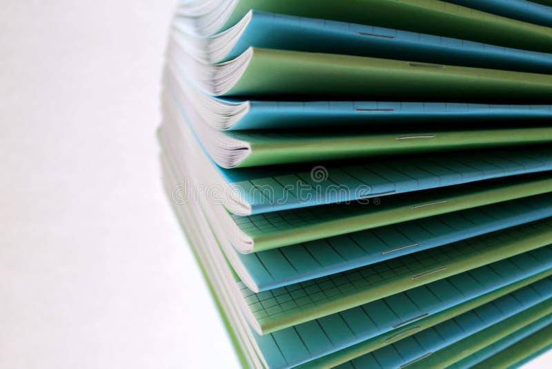 Tunn anteckningsbok för att skriva i den kulöra skolan arkivfoton