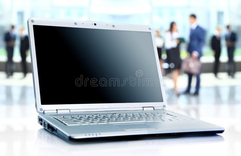Tunn bärbar dator på kontorsskrivbordet royaltyfri fotografi