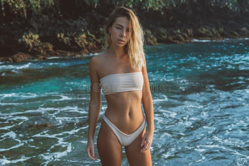 Tunn flicka i vita baddräktställningar i vattnet på den buskiga tropiska stranden, royaltyfria bilder