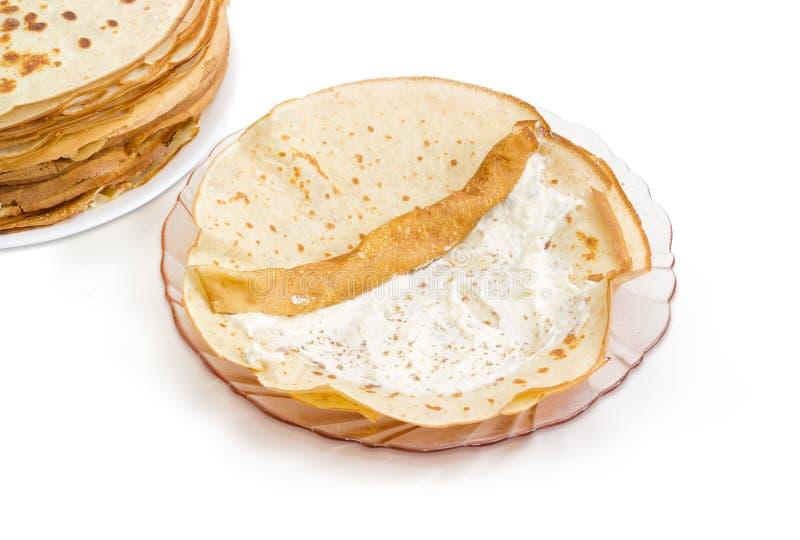 Tunn pannkaka under rullning upp med kesofyllning royaltyfri bild