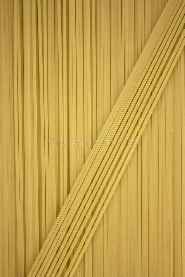 Tunn pasta som är ordnad i rader italiensk pastayellow Lång spagetti spagetti gör tunnare Matbakgrundsbegrepp fotografering för bildbyråer