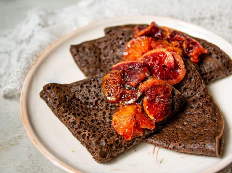 Tunna chokladpannkakor med blodapelsinsås på en vit platta på grå bakgrund med snör åt tyg Bunt av kräppar, ryss royaltyfria foton