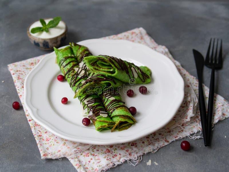 Tunna kräppar för mintkaramell av grön färg som vrids in i rör, med chokladsås, gräddfil, mintkaramellbladet och mandelkronblad p arkivbild