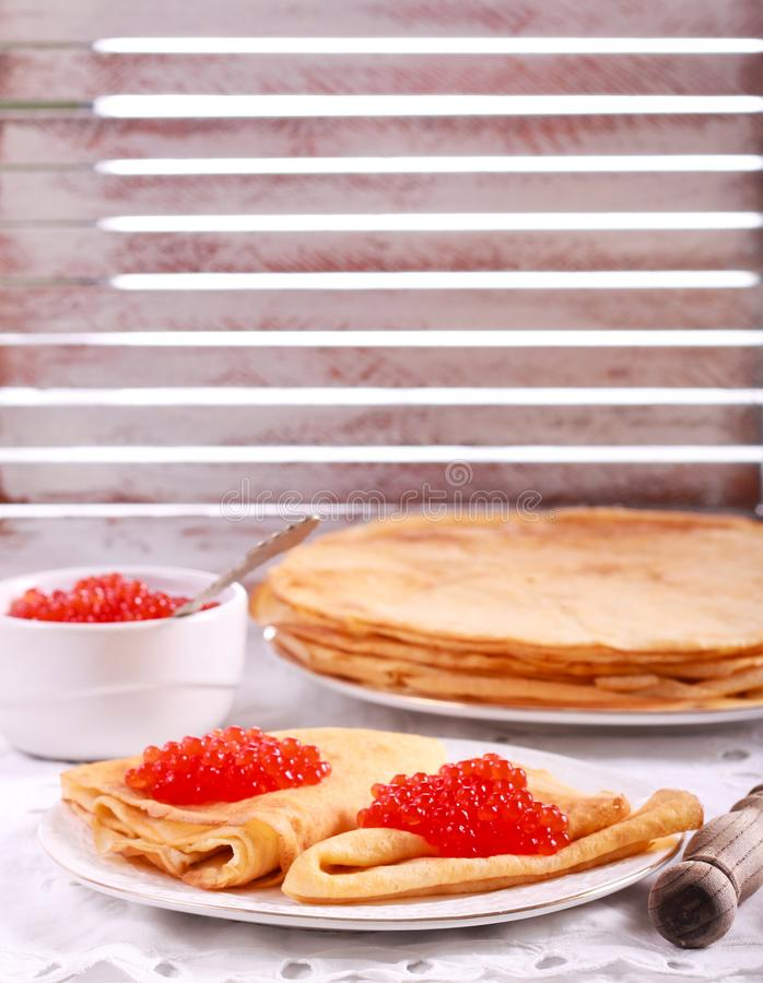 Tunna pannkakor med den röda kaviaren royaltyfria foton