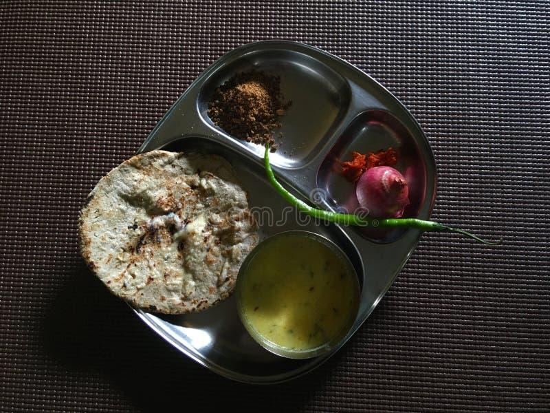 Tunnbröd för Bajra hirsroti Kadhi-med jaggeryonion och gräsplan-chili arkivfoto
