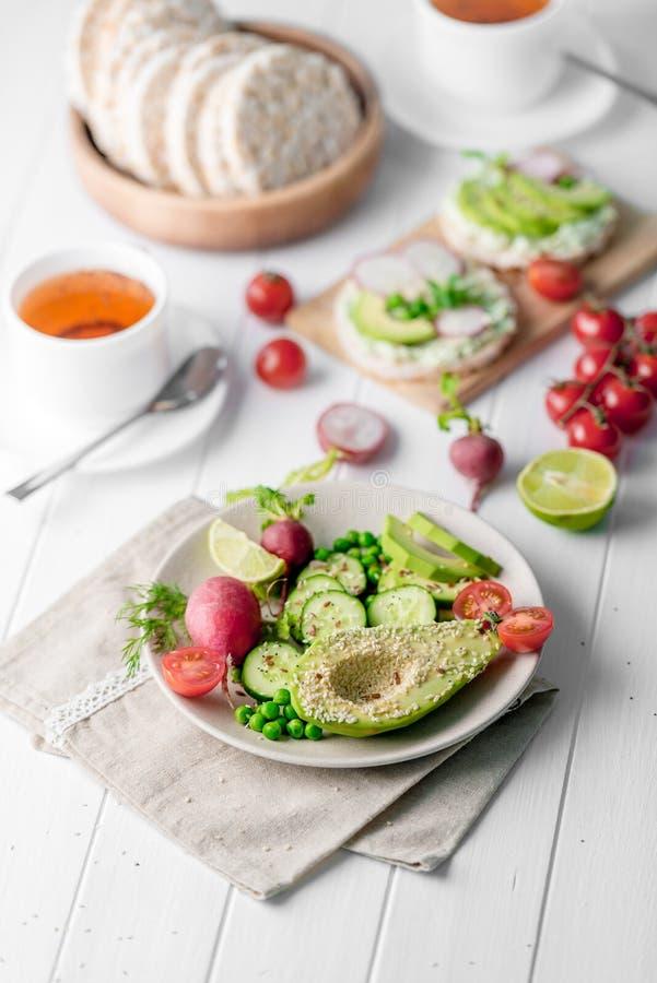 Tunnbröd med avokadot och raddish, kopp te royaltyfri fotografi