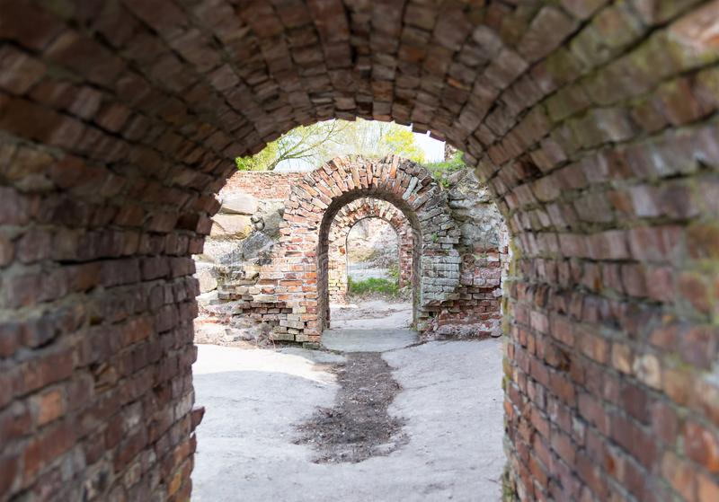 Tunnel arch building ruins brick building with cement floor, fragment of catacombs royalty free stock image