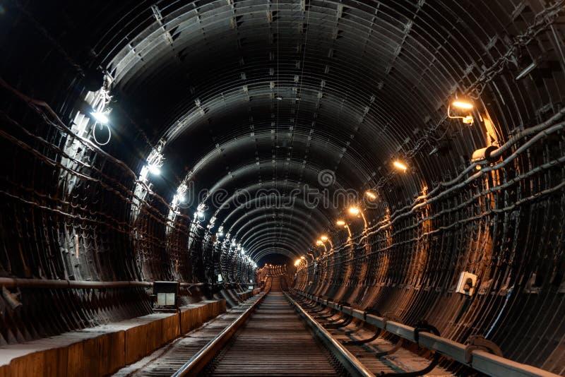 Tunnel circulaire droit de souterrain avec la tuyauterie et deux lumières différentes : blanc et jaune photo libre de droits