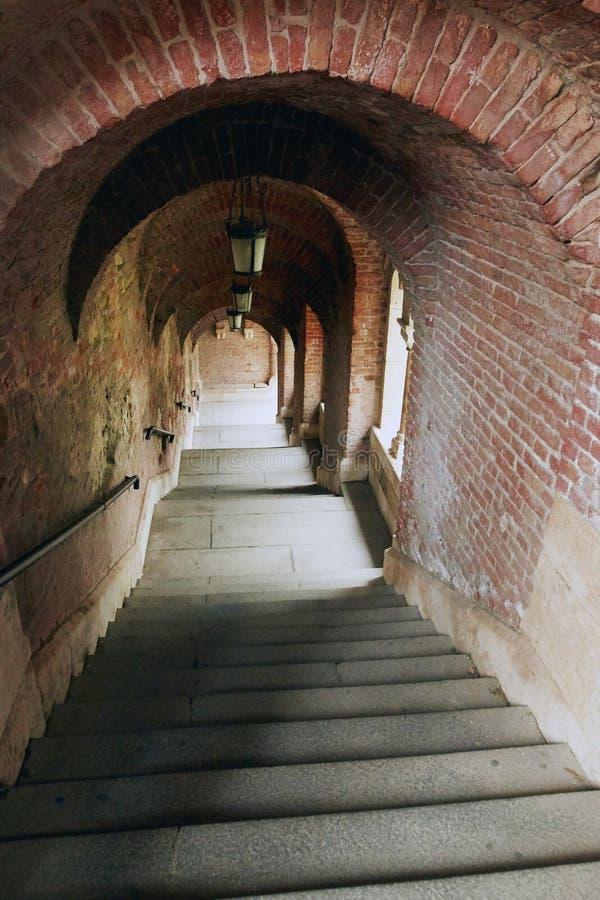 Tunnel del mattone con una scala che conduce giù fotografie stock