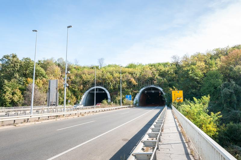 Tunnel on the end of the Liberty bridge with cars and road signs under the part of Fruska gora mountain. royalty free stock image