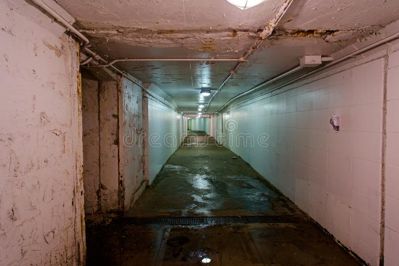 Tunnel, Industrial Walkway. A tunnel lit by vapor lamps or lights. Damp and wet with puddles on the floor. White walls and a long straight corridor in an urban royalty free stock photos