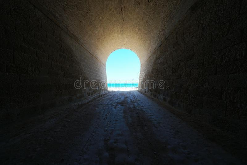 A tunnel leads to the seashore royalty free stock image