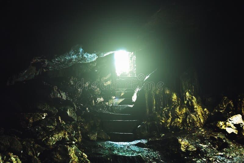 Tunnel met licht aan het eind, uitgang met stappen van het ondergrondse hol of kerker stock foto's