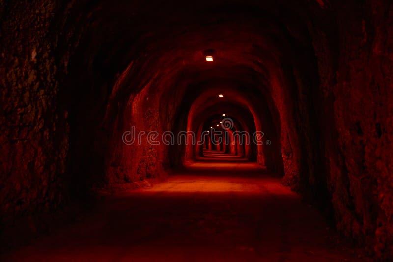 Tunnel rouge-foncé avec des projecteurs dans la roche photos libres de droits