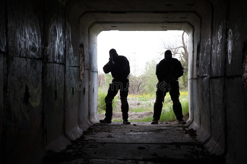 In the tunnel. Silhouette of special forces operators with weapons in the tunnel stock image