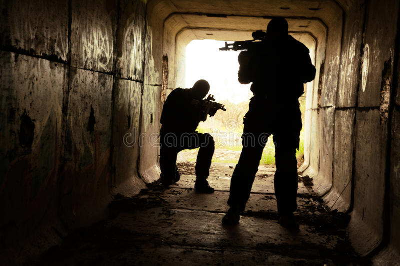 In the tunnel. Silhouette of special forces operators with weapons in the tunnel stock photography