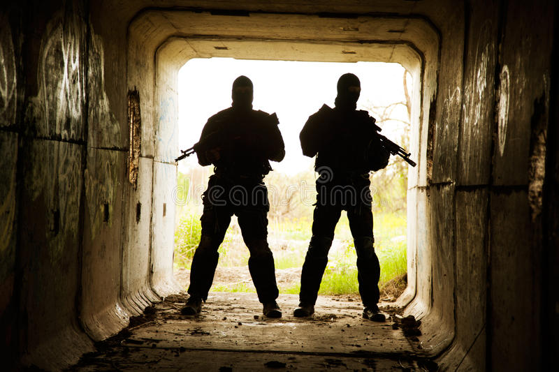 In the tunnel. Silhouette of special forces operators with weapons in the tunnel royalty free stock photo