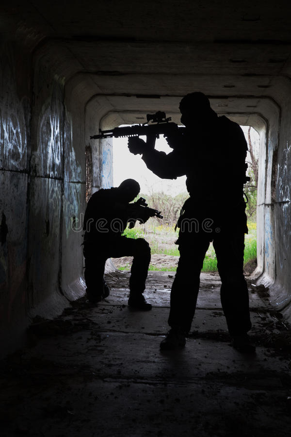 In the tunnel. Silhouette of special forces operators with weapons in the tunnel royalty free stock image