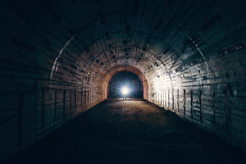 Tunnel souterrain abandonné rampant sombre ou couloir de chambre forte dans l'abri antiaérien et homme avec la lampe-torche, lumi image libre de droits
