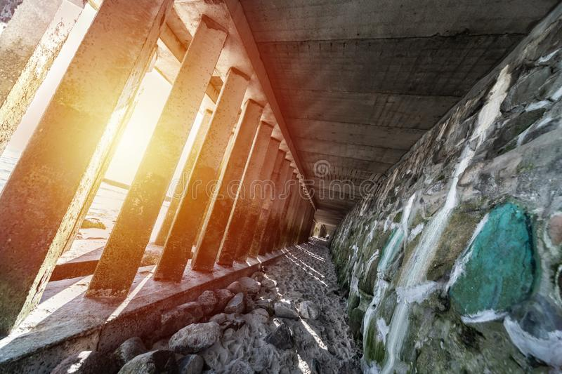 Tunnel under promenade near sea. Beautiful sunlight. Concrete pillars stone tunnel. Beach area for holidaymakers royalty free stock images