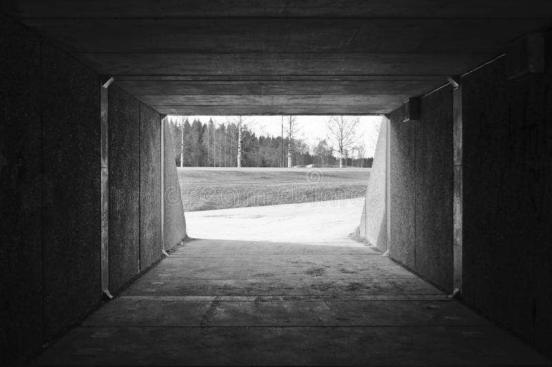 Tunnel walkway/bikeroad with lots of light coming in at the end. Fields and trees in the background. Photo in black and white. Nic. Tunnel walkway/bikeroad with royalty free stock photography