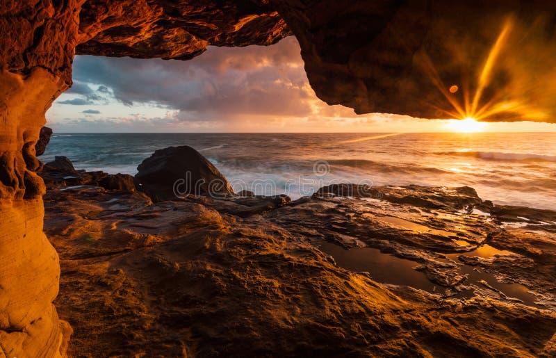 Tunnels côtiers de roche aux rebords de falaise avec la lumière du soleil de début de la matinée photographie stock